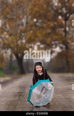 Lächelnde junge mit Regenschirm auf Landstraße - Stockfoto
