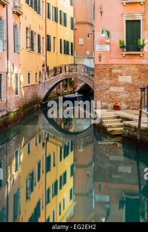 Malerischer Blick auf einen Kanal mit Gebäuden und steinerne Brücke spiegelt sich im Wasser, Venedig, Veneto, Italien - Stockfoto
