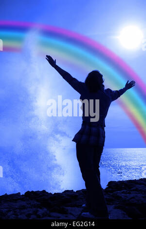 Silhouette einer einsamen Frau, hob die Arme in Ehrfurcht und Lob an die Kraft der Natur - Stockfoto