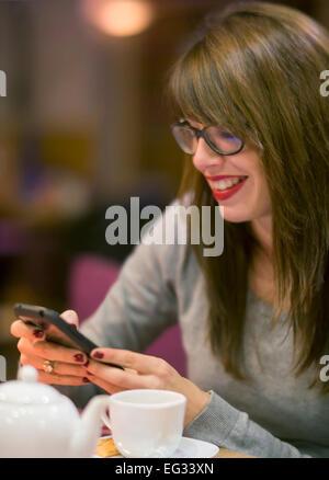 Schöne junge Frau, die Überprüfung ihres Mobiltelefons während ein heißes Getränk eines gemütlichen Cafés. - Stockfoto