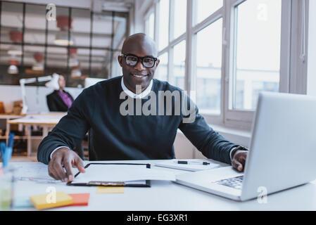 Porträt von zuversichtlich junger Mann an seinem Schreibtisch mit Laptop Papierkram zu tun. Afrikanische glücklich - Stockfoto
