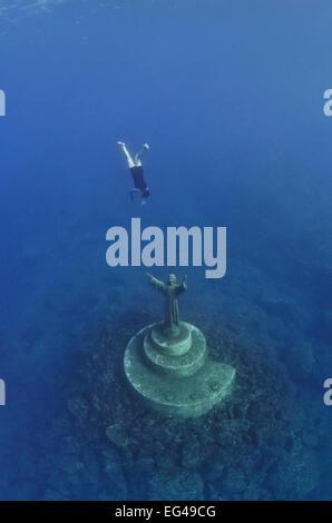 Ein Fischer schwimmt nach unten, tippen Sie auf die Statue Christus The Abyss (Cristo Degli Abissi) Glück in der - Stockfoto