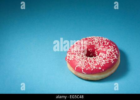Donut mit roten Glasur auf blauem Hintergrund mit Exemplar isoliert - Stockfoto