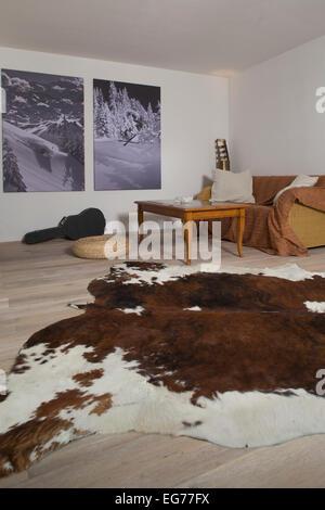 Wohnzimmer mit zwei Fotografien an der Wand und Kuh verstecken sich in den Vordergrund - Stockfoto