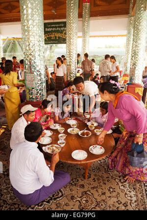 Eine burmesische Familie eine Mahlzeit im Rahmen einer religiösen Zeremonie; die Shwedagon-Pagode, Yangon, Myanmar - Stockfoto