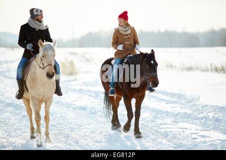 Glückliches Paar in Winterwear Reiten in natürlicher Umgebung - Stockfoto