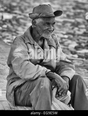 Ein älterer kubanischer Mann einen Cowboy Hut saß auf einem erhöhten Bordstein an einer Straßenecke in Trinidad, - Stockfoto