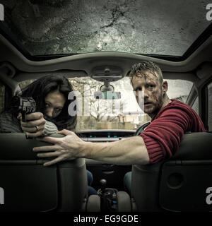 Paar im Auto mit Pistole - Stockfoto