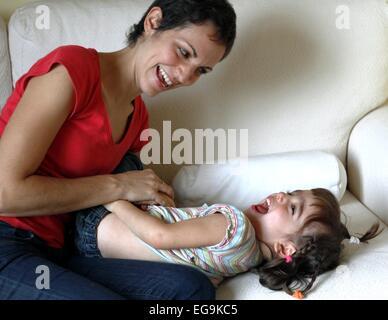 Mutter saß auf Sofa kitzeln ihre Tochter - Stockfoto