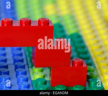 Teil einer Lego Konstruktion einer roten Brücke über einem blauen Fluss in eine grüne und gelbe Landschaftsmodell - Stockfoto