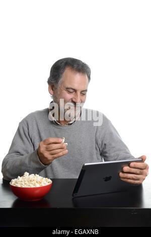 Mittleren Alter Mann mit einer Apple-Tablet iPad Luft beim Essen Popcorn zu Hause - Stockfoto