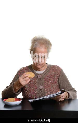 Mittlere gealterte Frau eine Zeitschrift liest, während des Essens Cookies zu Hause - Stockfoto