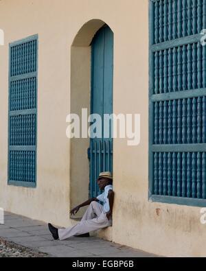 Eine kubanische Mann raucht eine Zigarre in einem Hauseingang an der Plaza Mayor in Trinidad, Kuba - Stockfoto