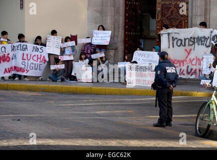 Eine Polizistin wacht über eine Studentendemonstration Universität, Merida, Yucatan, Mexiko - Stockfoto