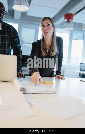 Weibliche Führungskraft Businessplan, ihr Team in einer Sitzung zu erklären. Frau zeigt ein Dokument einen Kollegen - Stockfoto