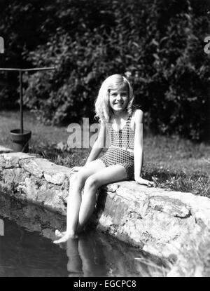1930S 1940S JUNGES MÄDCHEN SITZT AUF STEINMAUER SEE TEICH FÜßE IM WASSER TRAGEN BADEANZUG MIT GÜRTEL BLONDINE - Stockfoto