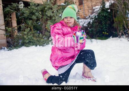 Kleine süße Mädchen stehen auf ein Knie im Schnee mit einem Schneeball in ihren Händen - Stockfoto