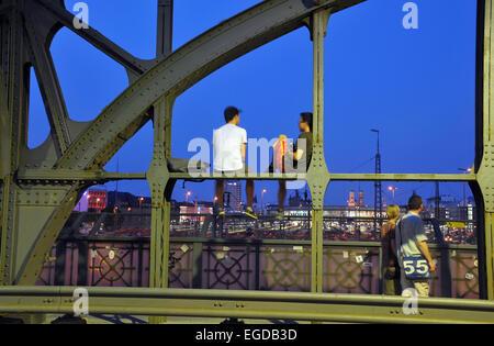 Leute sitzen auf der Hacker-Brücke am Abend, München, Bayern, Deutschland - Stockfoto