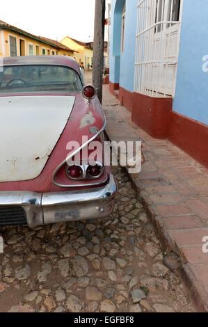 Ein kubanische Oldtimer im Detail gesehen in einer zentralen Straße von Trinidad und ein Huhn auf dem Bürgersteig - Stockfoto