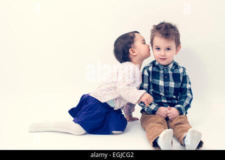 kleines Mädchen küssen ihr älteren Bruder auf die Wange, isoliert - Stockfoto