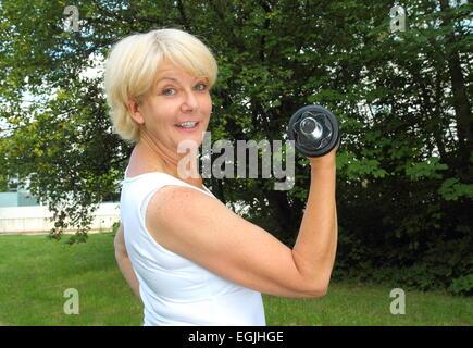 Eine ältere Frau, die dabei im freien Training in einem Park mit Hantel - Stockfoto