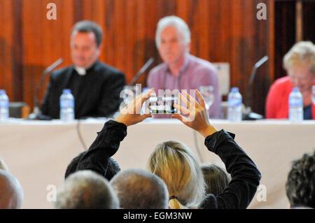 Eine Frau benutzt ihr Handy ein Foto von der Jury in einem politischen Gremium Talkshow zu nehmen. - Stockfoto