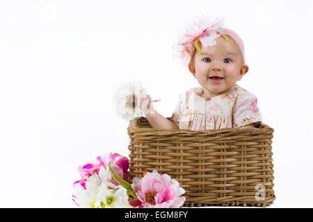 niedliche Baby in eine Blumenkleid sitzt in einem Blumenkorb - Stockfoto