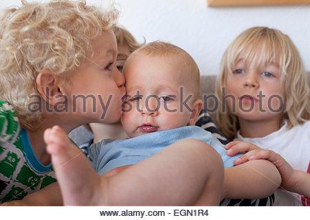 Kleiner Junge küssen seine entzückende Baby Bruder, Sankt Augustin, Deutschland - Stockfoto
