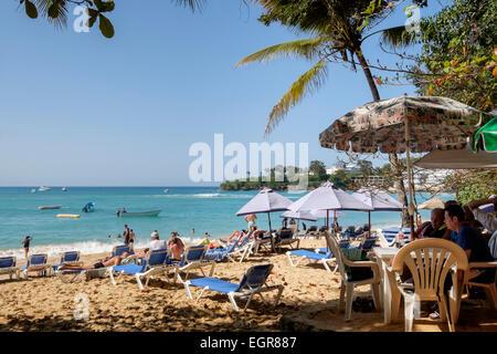 Strandbar und Touristen auf sandigen Strand mit Meer im Ferienort Sosua, Puerto Plata, Dominikanische Republik, - Stockfoto