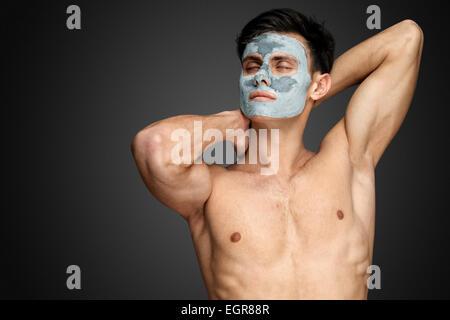 Porträt einer schönen entspannten jungen Mann mit einer Gesichtsbehandlung Schlamm Lehm Maske, Gesicht und Körper - Stockfoto