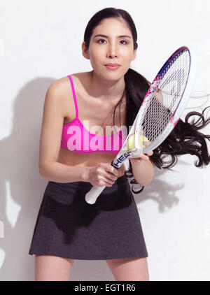 Junge Japanerin mit einem Tennisschläger in einem sportlichen Outfit auf weißem Hintergrund - Stockfoto