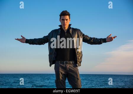 Hübscher trendige junger Mann feiern Natur an der Küste stehen direkt am Meer mit seinen Armen ausgestreckt zu betrachten - Stockfoto
