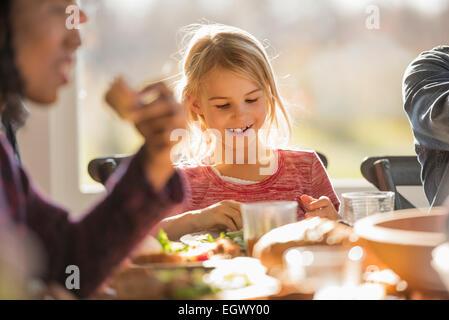 Eine Gruppe von Menschen, Erwachsene und Kinder, sitzen um einen Tisch für eine Mahlzeit. - Stockfoto