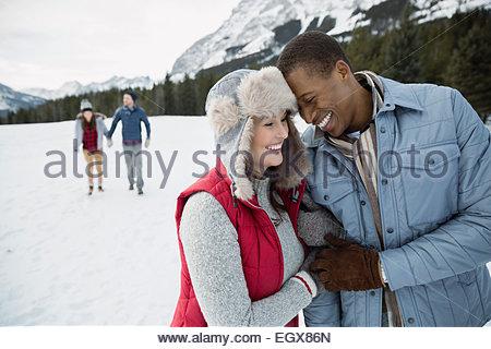 Paar umarmt und lächelnd in schneebedecktes Feld - Stockfoto