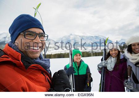 Lächelnde Familie mit Skiern in schneebedecktes Feld - Stockfoto