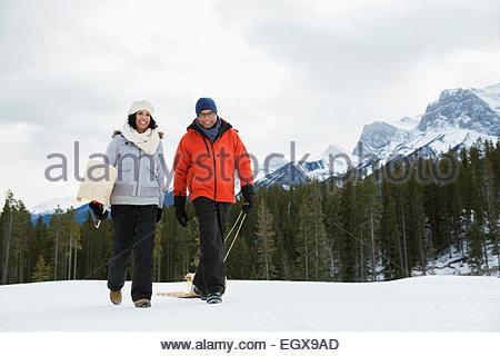 Paar mit Schlitten in schneebedeckten Feld unter Berg - Stockfoto