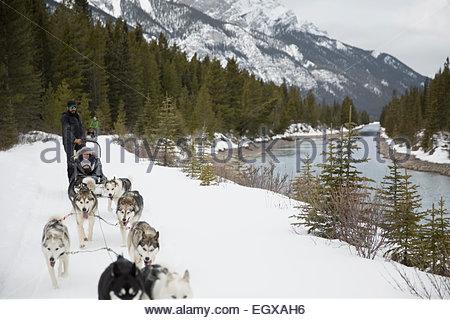 Hundeschlitten verschneiten Fluss unterhalb der Berge entlang bewegen - Stockfoto