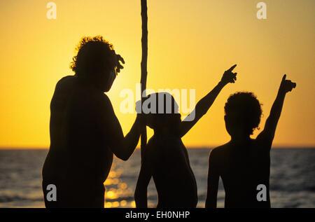 Aborigines mit einem Mast und Kindern zeigt auf den Himmel bei Sonnenuntergang, Darwin, Australien - Stockfoto