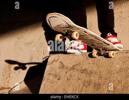 Blick auf schließen ein mans Skateboard und Füße, kurz bevor er auf einem Betonblock Tropfen. - Stockfoto