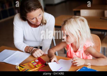 Lehrer helfen Mädchen an der Rezeption in Zeichnung - Stockfoto