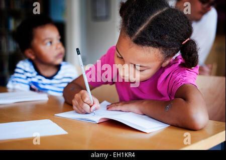 Mädchen schreiben in Buch im Klassenzimmer - Stockfoto