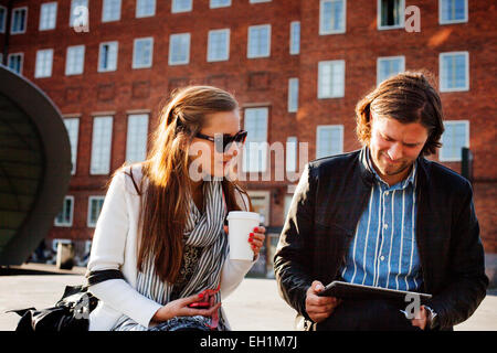 Geschäftsfrau hält Kaffeetasse während Kollege mit digital-Tablette gegen Gebäude - Stockfoto