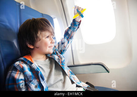 Lächelnde Knabe mit Spielzeug Flugzeug am Fenster - Stockfoto