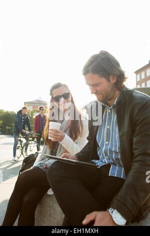 Geschäftsfrau Kaffeetrinken während der Geschäftsmann mit digital-Tablette in Stadt gegen klaren Himmel - Stockfoto