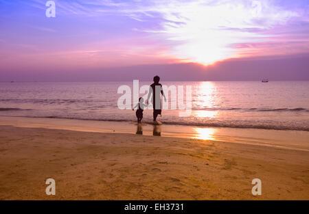 Glücklicher Vater und Sohn spielen am Strand bei Sonnenaufgang, Silhouette Schuss - Stockfoto