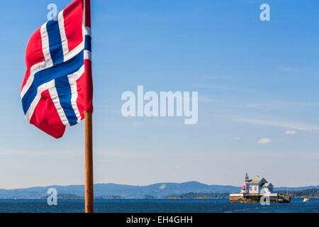 Norwegen, Oslo, Oslofjord, alten Leuchtturm Dyna Fyr (1874) in den Fjord mit norwegischer Flagge im Vordergrund - Stockfoto