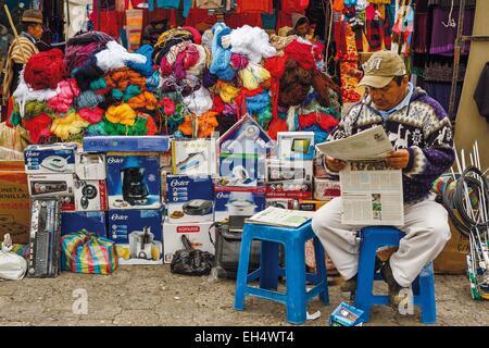 Ecuador, Cotopaxi, Zumbahua, das Dorf von Zumbahua Markttag, lesen die Zeitung vor seinem Geschäft Markt Händler - Stockfoto