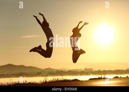 Fitness-paar springen glücklich bei Sonnenuntergang mit der Sonne im Hintergrund - Stockfoto