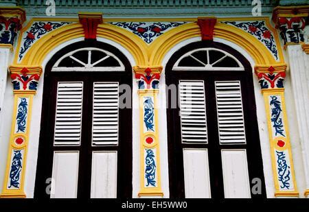 Melaka, Malaysia: Bunt bemalten pargetted Verputz Pilaster louvered Auslöser Rahmenfenstern auf chinesischen Shop - Stockfoto