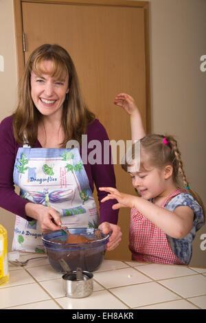 Mutter Karotte Kuchenteig mischen, während der fünf Jahre alte Tochter Uhren und vorgibt, ein Monster zu sein - Stockfoto